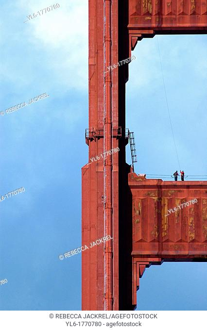 Two workers stand on the north tower of the Golden Gate Bridge