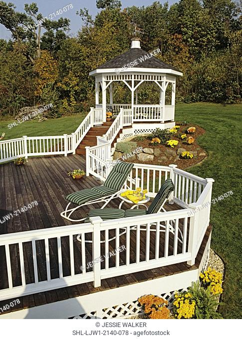 DECKS: White Gazebo at the end of deck. White railing on deck, green deck loungers, flowers around base of deck