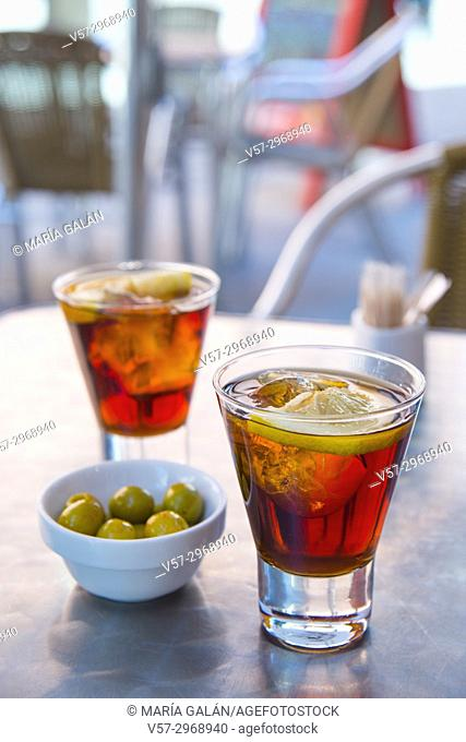 Spanish aperitif: two glasses of red vermouth with green olives in a terrace. Madrid, Spain