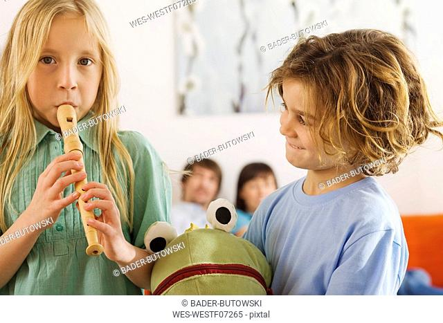 Boy 6-7 and girl 8-9, playing recorder, portrait