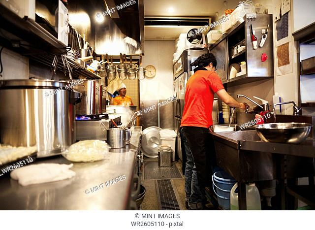 The ramen noodle shop. A chef working in a kitchen preparing food using a stove and large pans