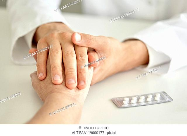 Close-up of doctor holding patient's hand