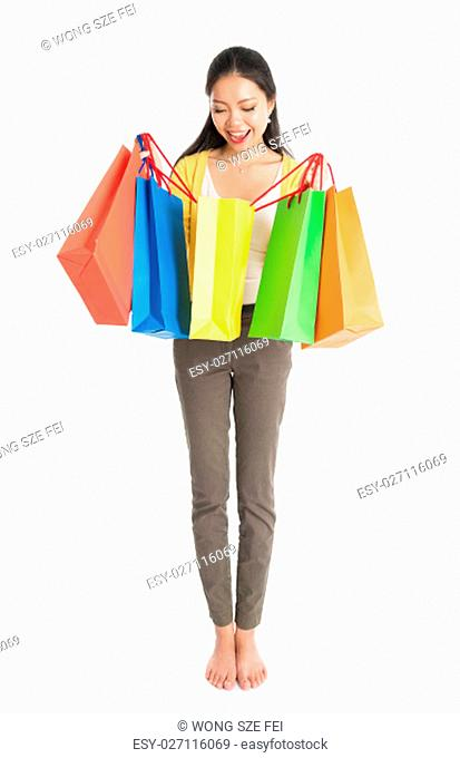 Happy young Asian female shopper, hands holding shopping bags and smiling, full length isolated standing on white background