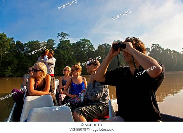 Tourists enjoy safari by boat in the KINABATANGAN RIVER WILDLIFE SANCTUARY which is home to many wildlife species - SABAH, BORNEO - , 05/04/2014