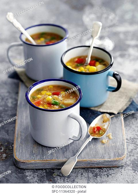 Thick quinoa and sweetcorn soup in enamel cups