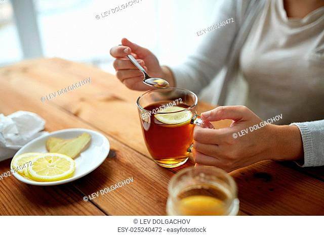 healthy food, eating and ethnoscience concept - close up of woman adding honey to tea cup with lemon and ginger