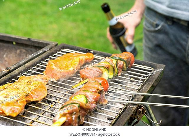 Man holding beer bottle at barbecue grill with meat