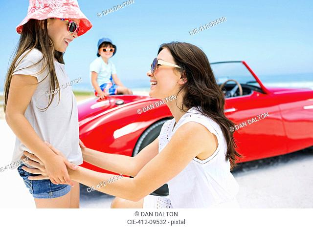 Mother and daughter smiling on beach near convertible