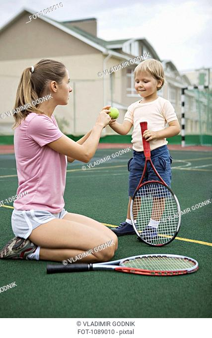 A mother teaching her young son tennis