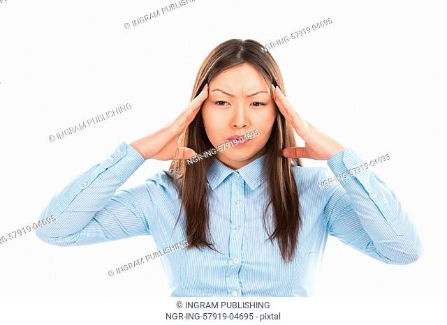 Beautiful Asian business woman with headache holding head in pain over white background