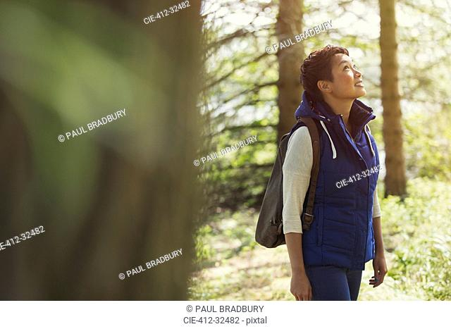 Woman hiking with backpack looking up in woods