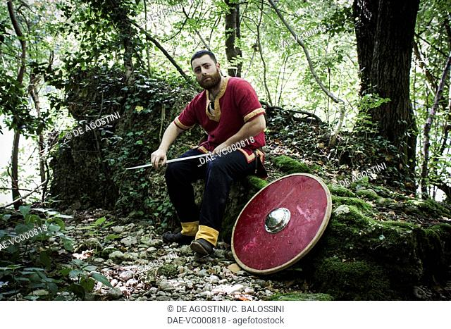 Langobard warrior carrying a shield and spear during a hunt expedition. Northern Italy, 6th century. Historical reenactment