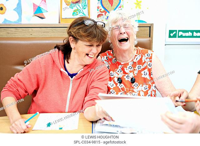 MODEL RELEASED. Dementia art therapy participants. Woman with dementia (right) and a community worker (left) at an art therapy group