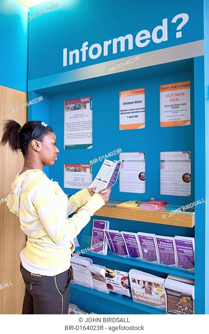 Young woman looking at information leaflets in the reception area at her sports leisure centre