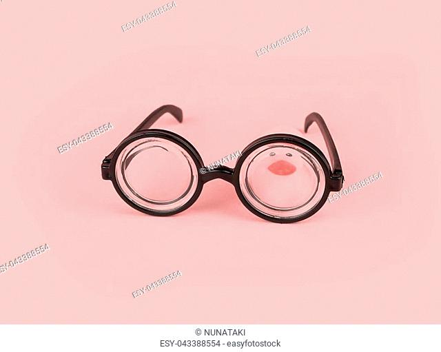 Funny goggles with round glasses on pink background and yellow rubber duck. April fool's day greeting card concept, education, school time, copy space