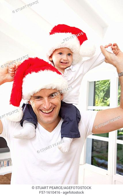 One year old boy on his fathers shoulders at Christmas time