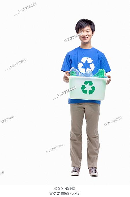 Portrait of young man holding recycling bin, studio shot