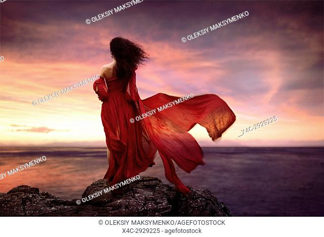 Beautiful artistic portrait of a young woman in red long summer dress flying in the wind standing on a rocky shore in sunset looking at the ocean, rear view