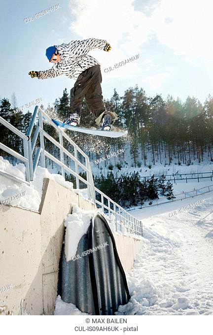 Mid adult male snowboarder jumping backwards from railings