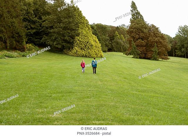 Two children walking in a huge and beautiful green park