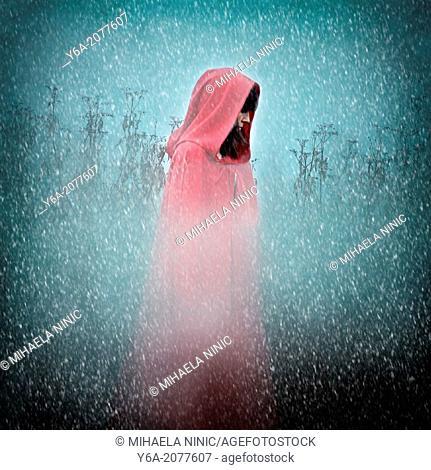 Woman wearing red cloak walking outdoors in winter storm