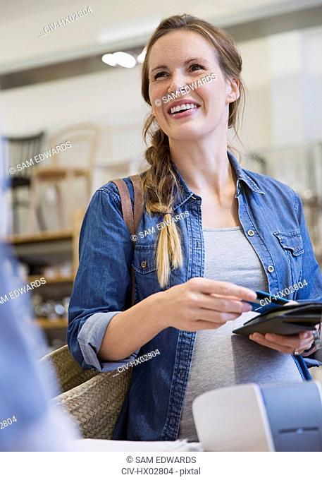 Smiling pregnant woman shopping, paying with credit card in shop