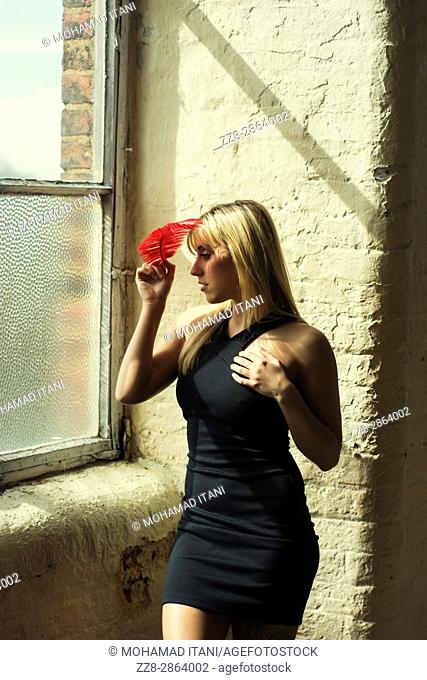 Young woman holding a red feather looking out of the window