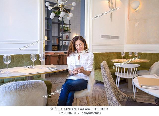 woman with white shirt and jeans, sitting in restaurant, using mobile phone reading, surfing internet, typing or messaging