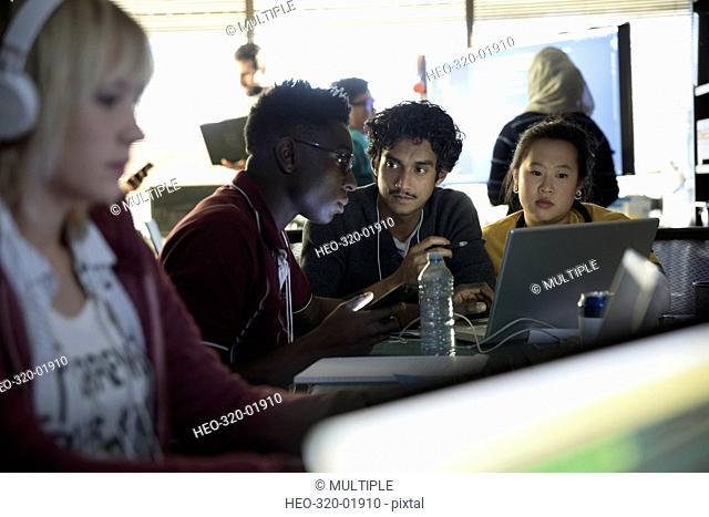 Hacker team working hackathon at laptop in dark office