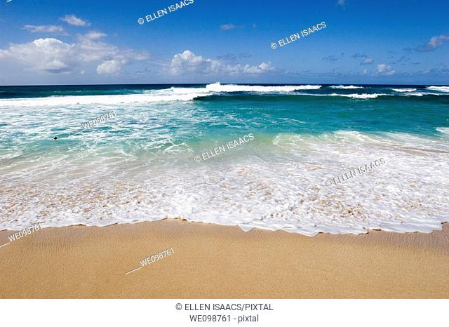 Waves breaking on a sandy beach on Oahu Hawaii with turquoise water of Pacific Ocean and deep blue sky  Sunset Beach, Oahu, Hawaii
