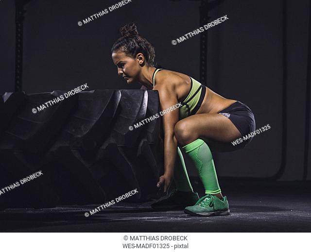 Young woman exercising with a tractor tyre