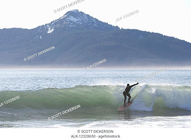 Surfer riding a wave along the Kenai Peninsula Outer Coast, South-central Alaska, USA