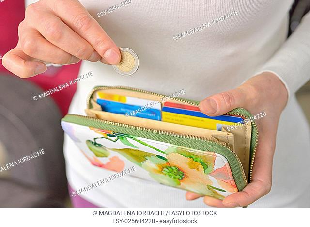 Woman hands counting coins and her wallet