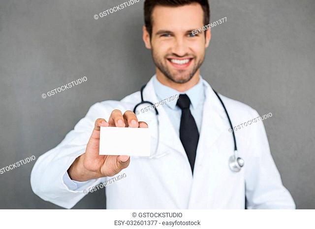 Trusted family doctor. Smiling young doctor in white uniform stretching out his business card while standing against grey background