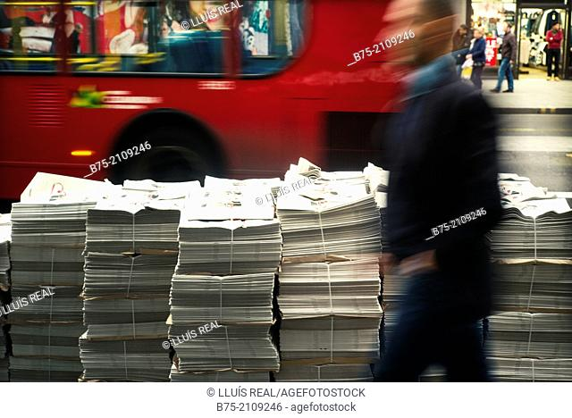 Plenty of free newspapers, Evening Standard, stacked on the street with an unrecognizable man walking and bus in the background
