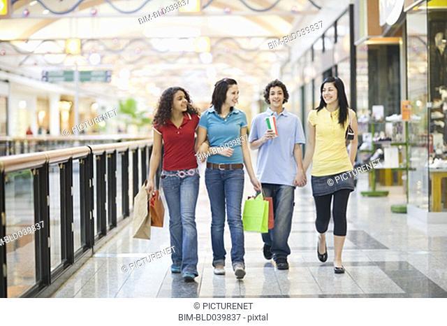 Multi-ethnic teenagers walking in mall
