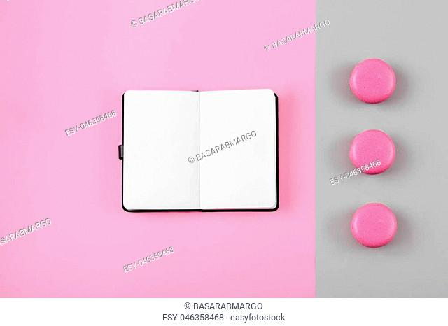 Macaron, clean notebook, eyeglasses on pink table from above. Female working desk. Flat lay style