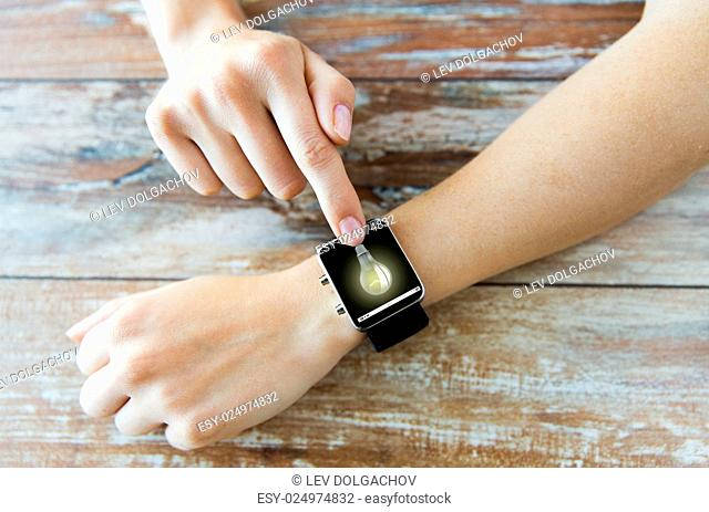 business, modern technology, startup, idea and people concept - close up of female hands setting smart watch with light bulb on screen on wooden table