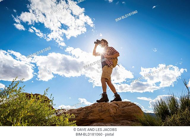 Hispanic man using binoculars on rock formation