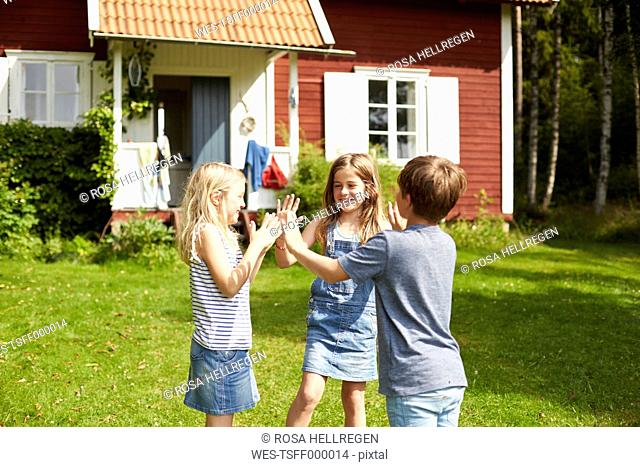 Sweden, three children playing on a meadow in front of holiday home