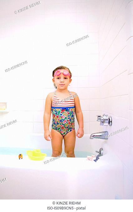 Portrait of girl wearing swimming goggles standing in bath