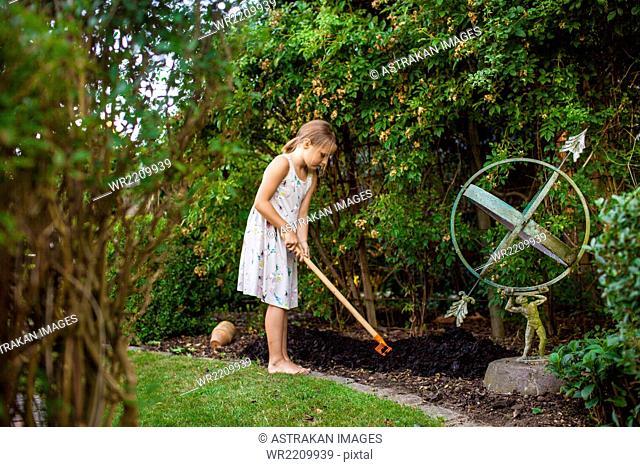 Full length of girl spreading fertilizer in backyard