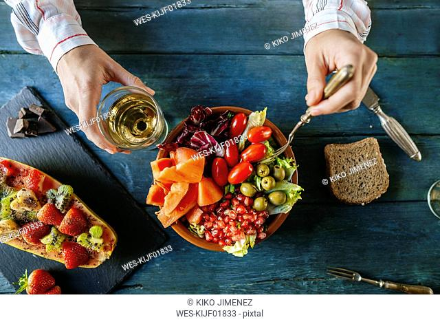 Close-up of woman's hands eating salad wit tomato, pomegranate, papaya and olives, papaya with fruits and with wine glass