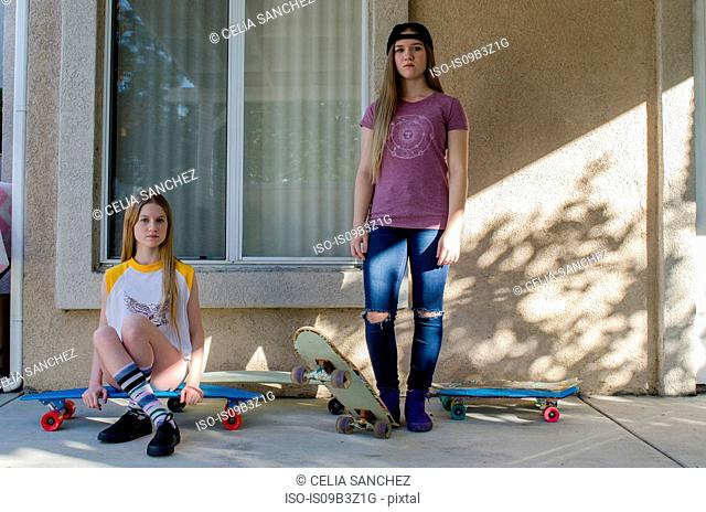 Portrait of two teenage skateboarder sisters on porch