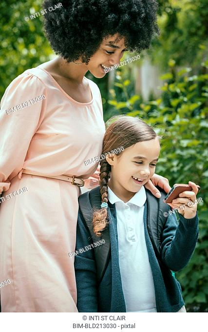 Mixed race mother and daughter using cell phone together