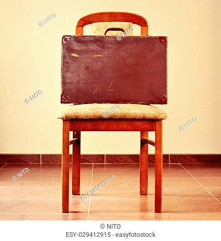 an old brown suitcase on a worn and retro chair