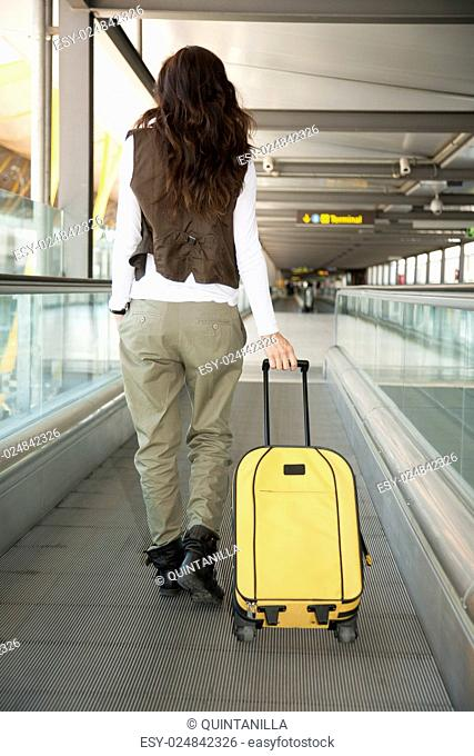 woman with vest walking with yellow suitcase at walkway inside airport hall