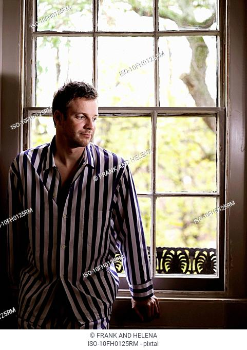 Man sitting by window in his pajamas