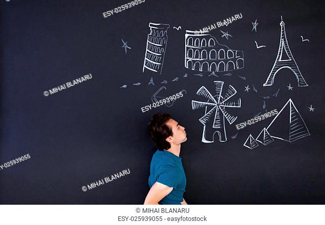 Young man playing with a draw that shows the world attractions. Large copy space on left