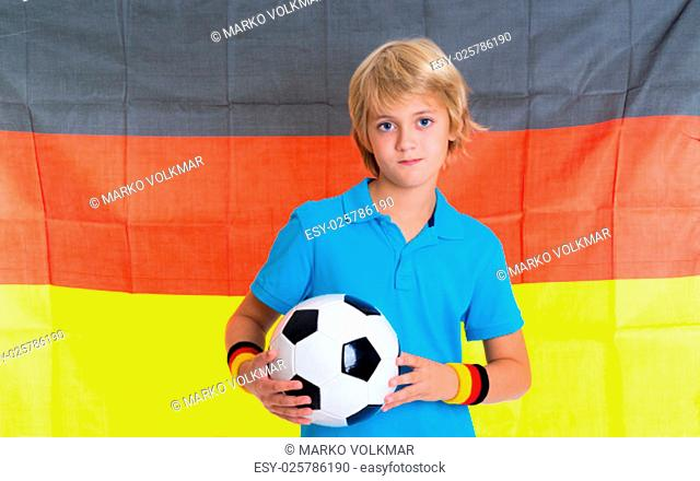 blond boy with soccer ball in front of german flag